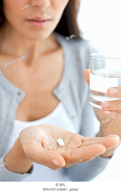 MODEL RELEASED. Young woman taking medicine