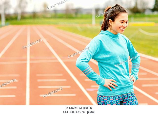 Portrait of young girl on running track, smiling