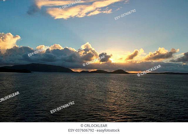The sun peaks through a cloudy sky over the ocean