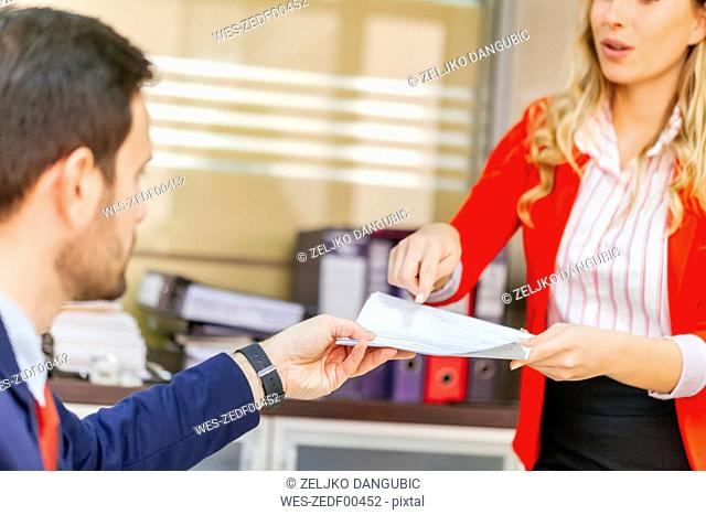 Secretary handing over document to businessman in office