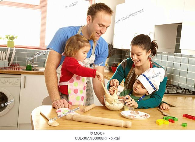 Young family cooking together in kitchen