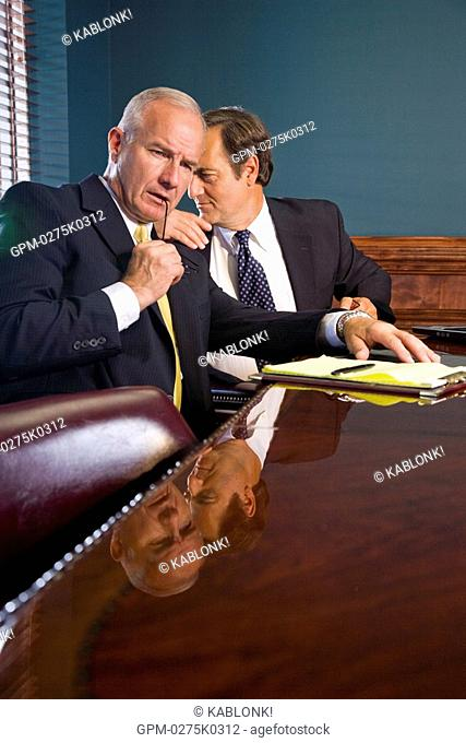 Two corporate executives having private conversation in conference room