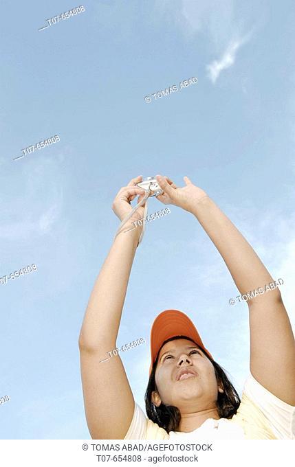 Latino woman holding digital camera