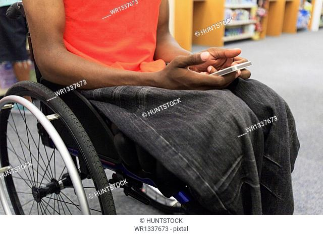 Man with spinal meningitis in a wheelchair using cell phone