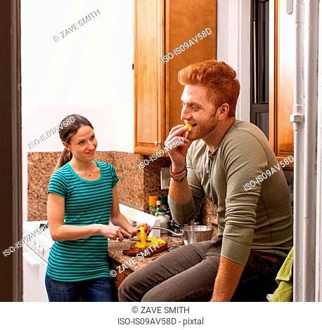 Couple in kitchen preparing meal smiling