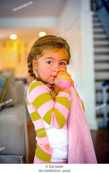 Girl with comfort blanket in living room at bedtime, portrait