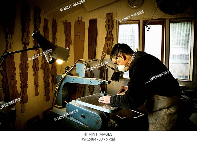 A man working in a furniture maker's workshop, using a machine saw