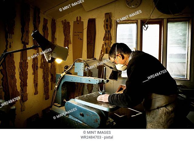 A man working in a furniture maker's workshop, using a machine saw