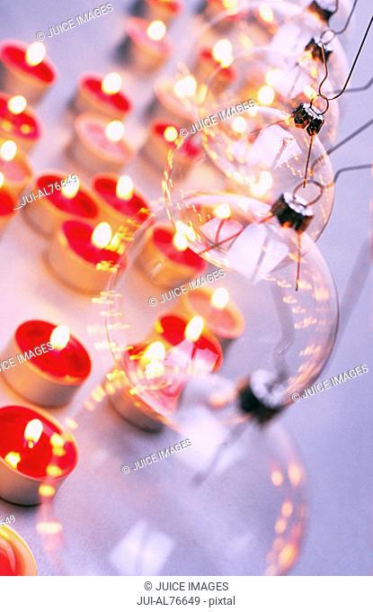 High angle view of burning tea candles below Christmas bulbs