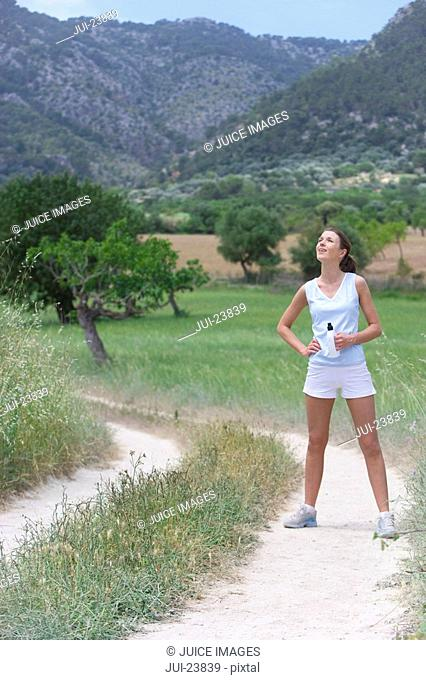 Female runner standing with water bottle on rural path