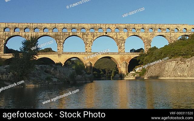 Pont du Garde, France : static shot of the Nimes Roman aqueduct crossing the Gardon River in early morning sun