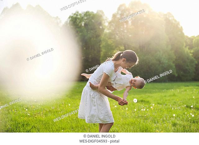 Mother and daughter playing on meadow in summer