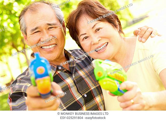 Senior couple with water pistols