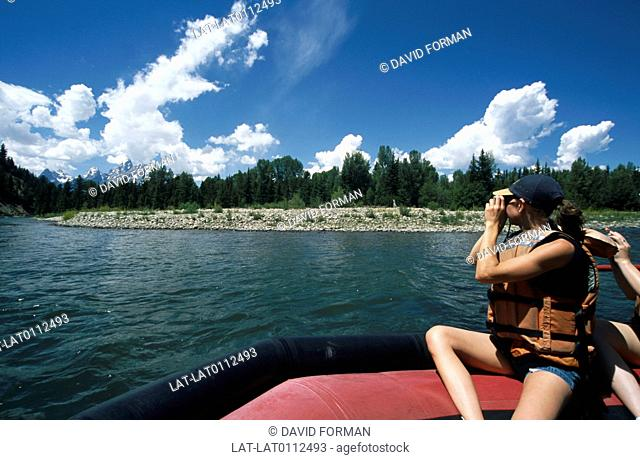 The Snake River running through the national park. A woman in an inflatible boat taking a photograph of the mountains