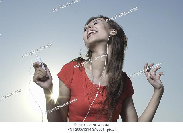 Young woman listening to an MP3 player and laughing
