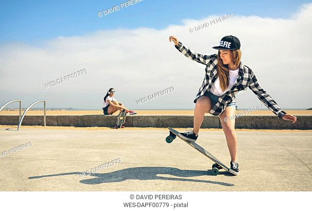Young woman longboarding while her friend watching her