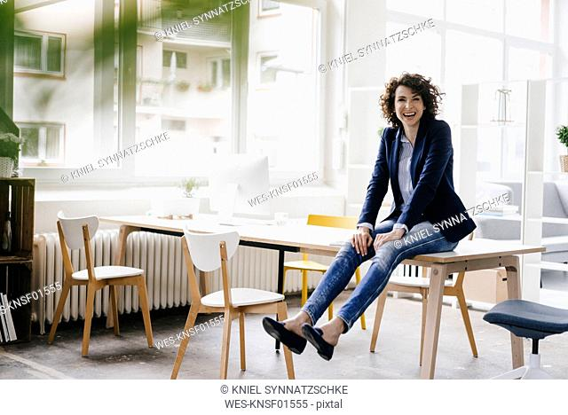 Businesswoman in office sitting on desk, having fun