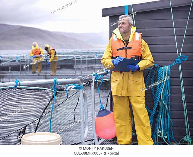 Worker using clipboard at fish farm