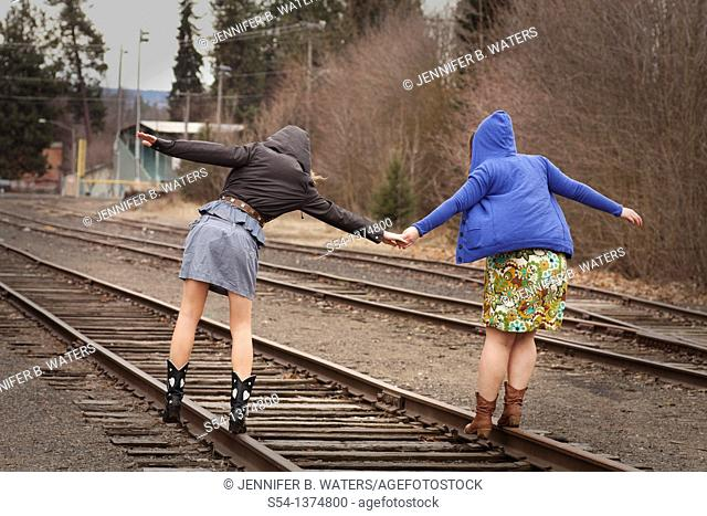 Two young women walking together on railroad tracks