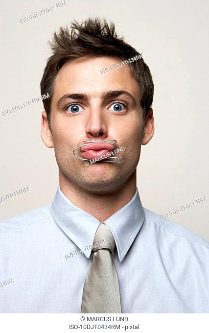 Business man with paper clip around lips