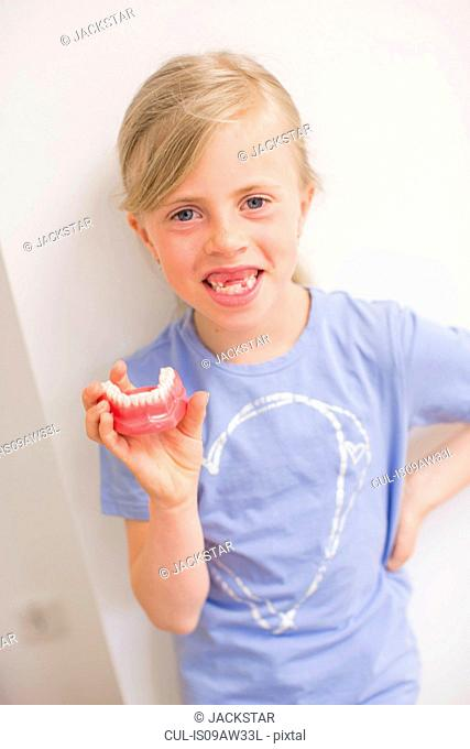 Girl with missing teeth holding dentures looking at camera smiling