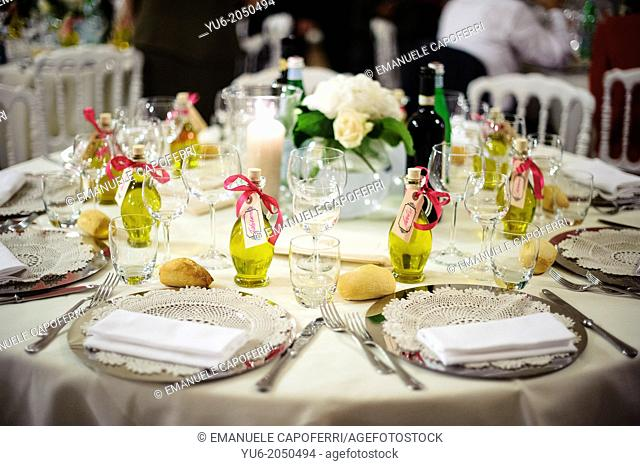 Table set for wedding dinner, with bottles of olive oil