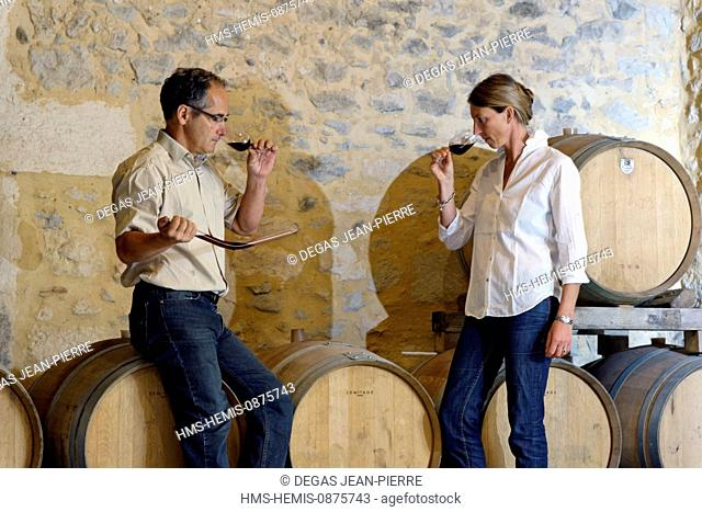 France, Herault, Saint Aunes, Chateau les Mazes domain, sampling wine in a barrel since the pipette in a cellar for tasting, owners Dorothee and Bernard Bouchet