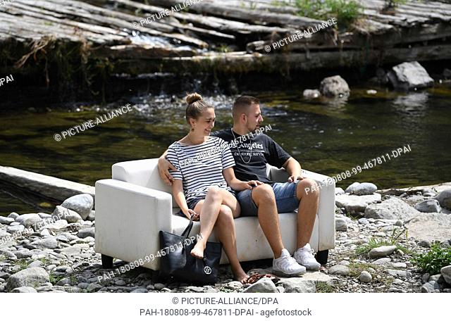 08 August 2018, Germany, Freiburg: Sandro and Antonia enjoy their lunch break on a sofa in the almost dried out Dreisam. Photo: Patrick Seeger/dpa