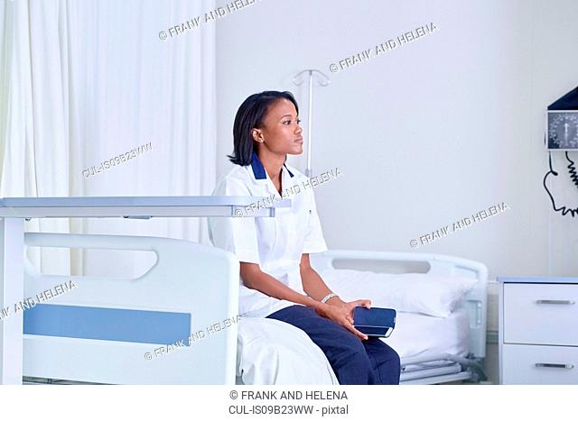 Female medic sitting gazing from hospital bed