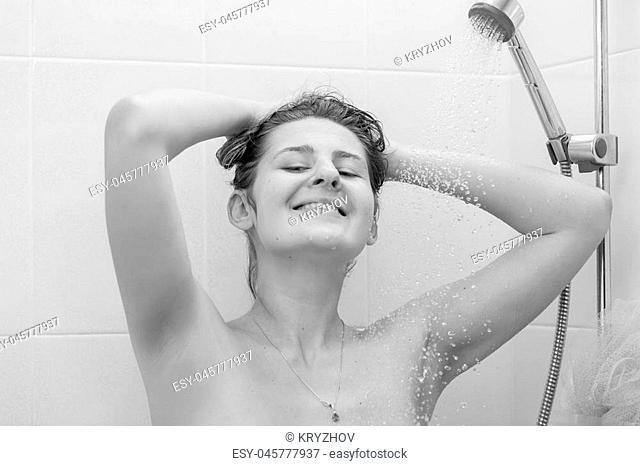 Black and white portrait of beautiful smiling woman washing hair at shower