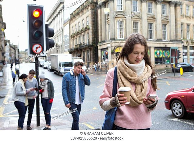A young woman can be seen walking along a city street with a smart phone. Other young adults are in the background using smart phones