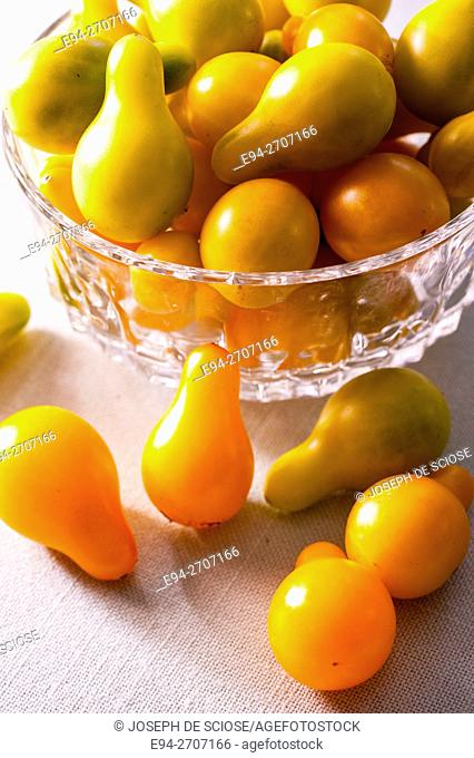 A close up of a bunch of Yellow Pear tomatoes in a bowl and a table