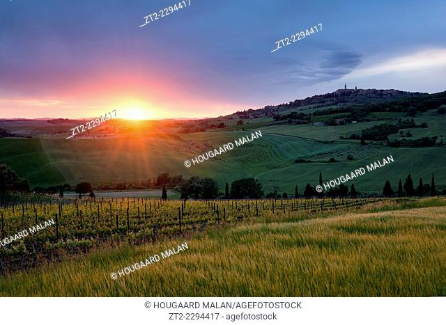 Landscape photo of a beautiful sunset over the rolling hills of Tuscany, with Pienza on the hilltop in the right. Val D'Orcia, Tuscany, Italy