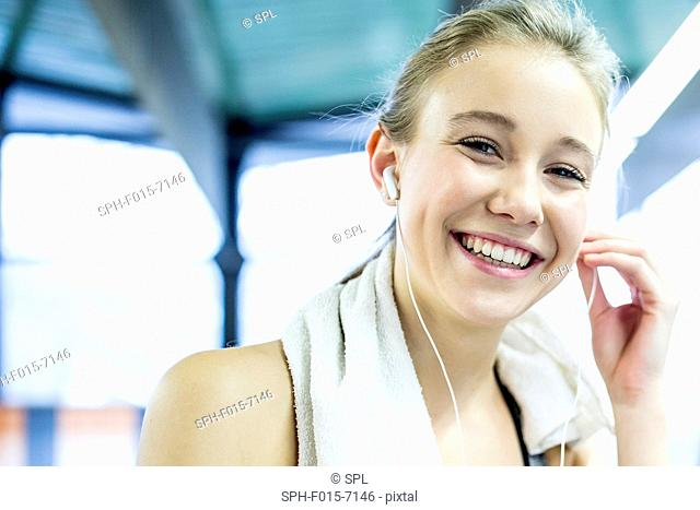 MODEL RELEASED. Young woman in gym wearing arm band and adjusting headphones, portrait
