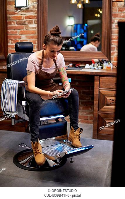 Hairdressers in barber shop texting on smartphone