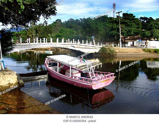 a pink boat crossing a paraty bridge