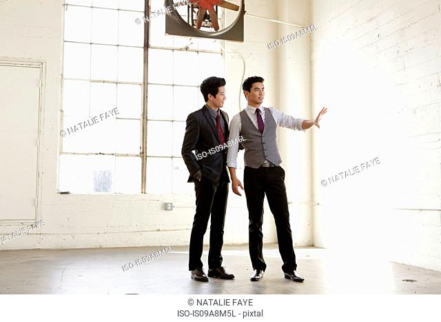 Two young business men meeting in empty office