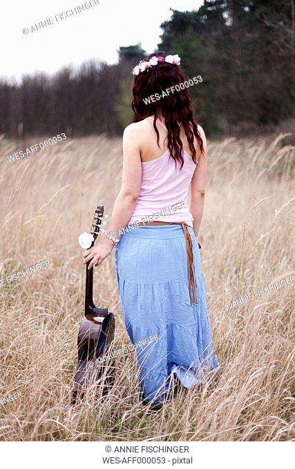 Germany, Young woman with guitar