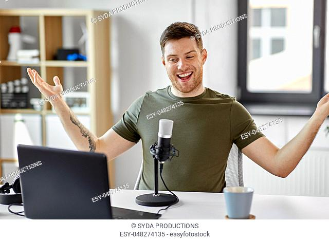 man with laptop and microphone at home office