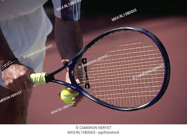 male tennis player holding racket and ball