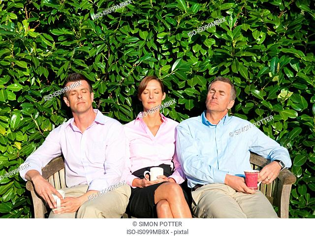 Three businesspeople sitting on bench, asleep
