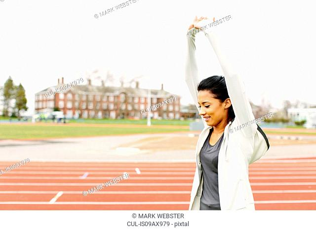 Young woman on running track, stretching