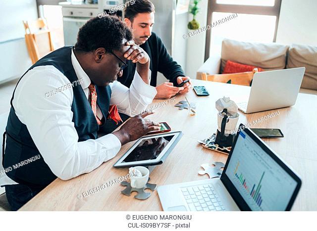 Businessmen using smartphone in loft office