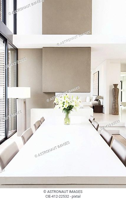 Modern white and beige dining room with large table and lilies in vase