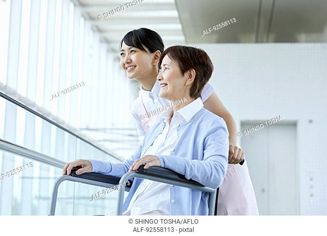 Young Japanese caregiver taking care of elder patient