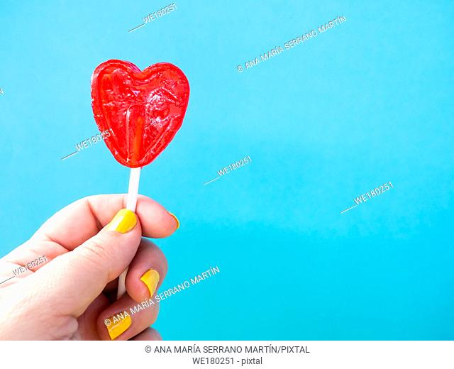 A woman with yellow painted nails with a red lollipop in her hand and blue background