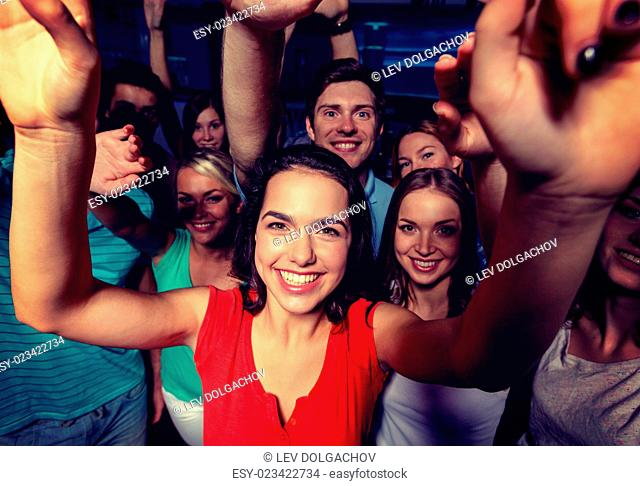 party, holidays, celebration, friends and people concept - smiling friends dancing and waving hands in club