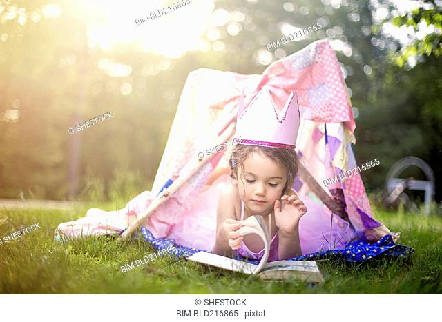 Girl reading in tent in backyard