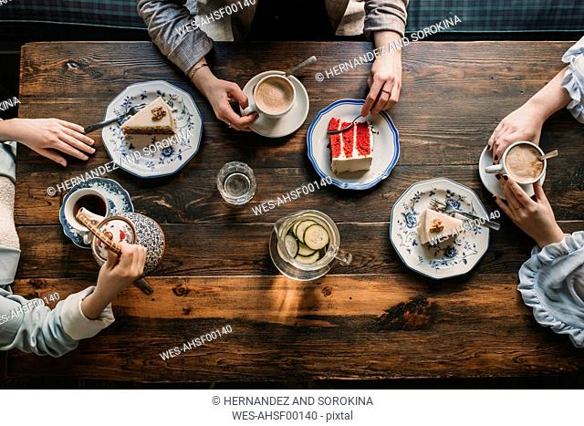 Top view of friends sitting at wooden table in a cafe