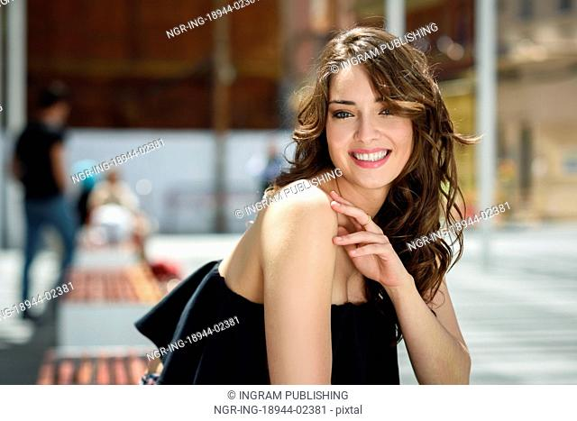 Beautiful young woman with blue eyes smiling in urban background. Girl wearing summer clothes